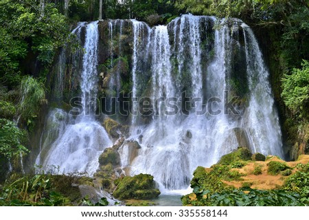 Waterfall in a lush rainforest. Beautiful waterfalls or cascades in El Nicho, El Nicho waterfall, in Scambray mountains. Cienfuegos province, Cuba. - stock photo