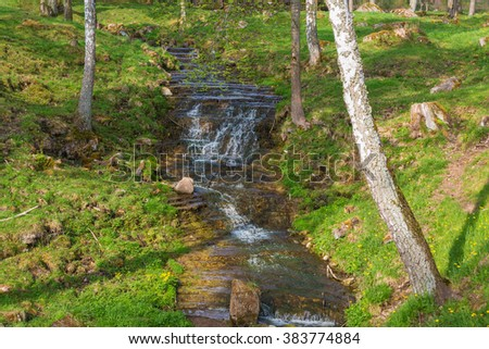 Waterfall in a ravine in spring - stock photo