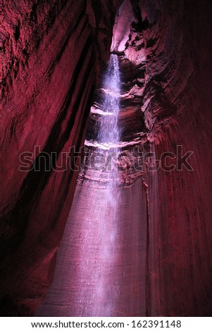 Waterfall in an underground cavern with colored lights. - stock photo