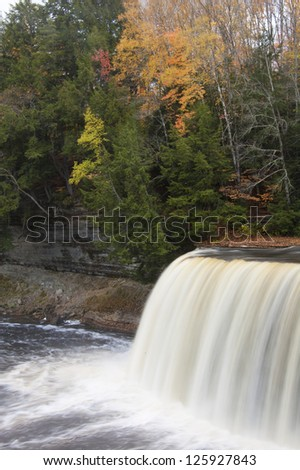 Waterfall in forest with autumn colors vertical, close up
