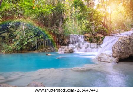 Waterfall in rain forest wit rainbow (Tat Kuang Si Waterfalls at Luang prabang, Laos.) - stock photo