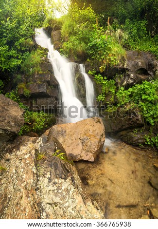 Waterfall in summer canyon. Natural landscape - stock photo