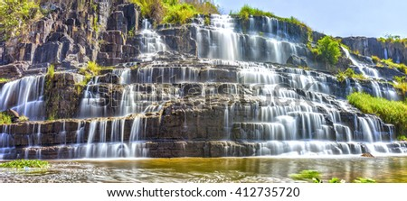 Waterfall in sunshine with water flowing down stairs step by creating folds like silk, beneath swirl all scraped up the beauty nature in Lam Dong, Vietnam - stock photo