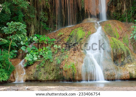 Waterfall in Thailand. Phu Sang waterfall is 35 degree Celsius water temperatures that flows from a limestone cliff 25 meters high. - stock photo