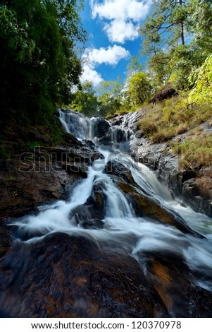 waterfall in the jungle against the dark blue sky and clouds - stock photo