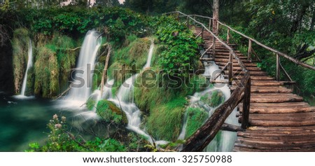 Waterfall in the lush green forest with long wooden stairway. - stock photo