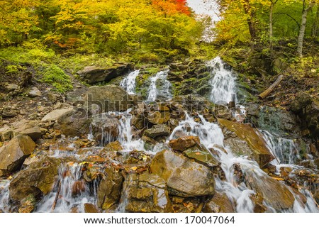 Waterfall in the mountains, autumn landscape - stock photo