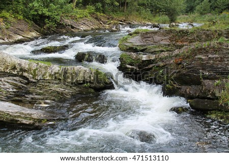 waterfall in the rocky valley of wild mountain river Ostravice