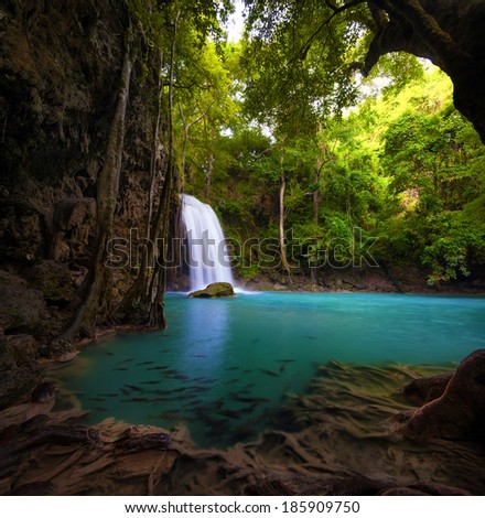 Waterfall in tropical forest. Beautiful nature background. Jungle trees and blue water of mountain river in national park in Thailand, Asia.  - stock photo