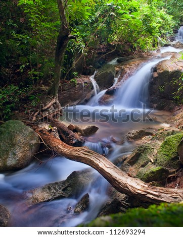 Waterfall in tropical forest. Mountain river, stones with moss and green trees - stock photo