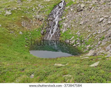Waterfall into a small lake without an outflow in the French Alps