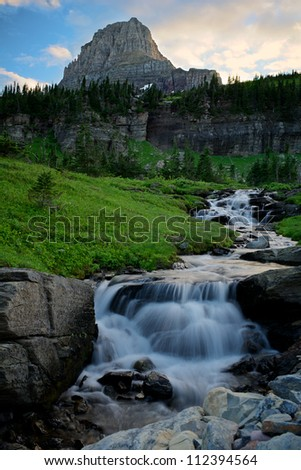 Waterfall landscape with mountain in the background.