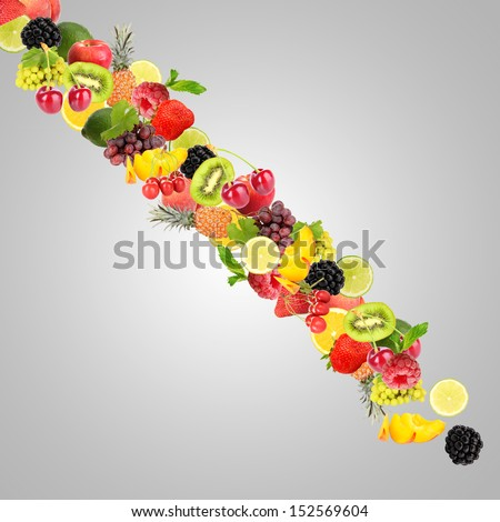 Waterfall of fruit and berries on gray background - stock photo
