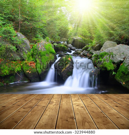 Waterfall on a mountain creek. In the foreground a wooden planks. - stock photo