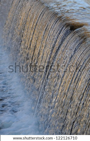 Waterfall over dam - stock photo