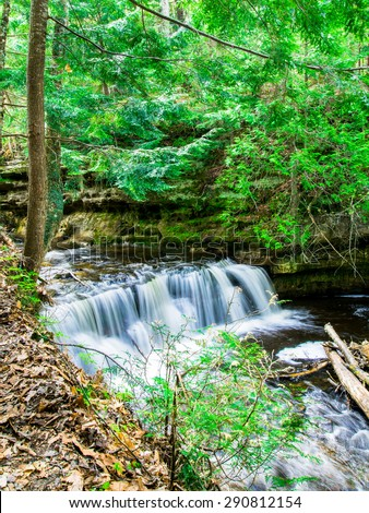 Waterfall over natural rocks, landscaping element. Gentle Mosquito water fall at Munising, Michigan - stock photo