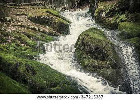 Waterfall rapids with water frozen in time splashing against mossy rocks