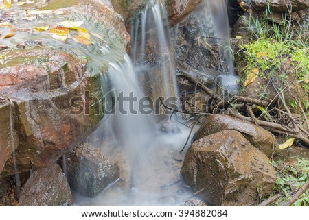 Waterfall small  Beautiful  with soft flowing water and large color stone - stock photo