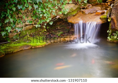 Waterfall spilling into coy fish or goldfish pond - stock photo