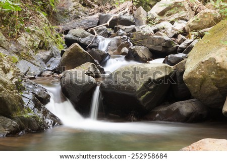 Waterfall that flows down from the mountains. Streams of water flowing down from the mountains. There is always a small stone waterfall. - stock photo
