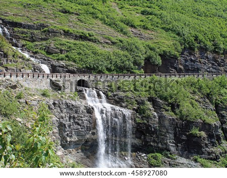 Waterfall Under a Roadway in Glacier National Park - stock photo