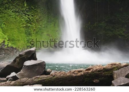 Waterfall with emerald pool in rainforest - Catarata Rio Fortuna, La Fortuna, Alajuela province, Costa Rica - stock photo