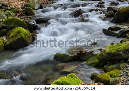 Waterfall with mossy rocks - stock photo