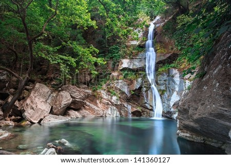 Waterfall with small lake surrounded by trees