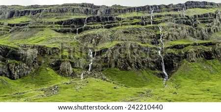 Waterfalls cascading down the mountain in east Iceland - stock photo