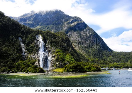 Waterfalls in Milford Sound New Zealand with boats anchored
