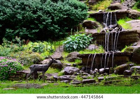 Waterfalls in public garden and statue of roe. Tallinn, Estonia. - stock photo