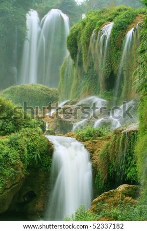 waterfalls on rocks in green spring - stock photo