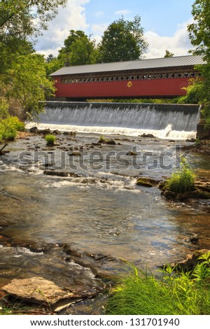 Waterfalls on the Walloomsac River below the historic Paper Mill Village Covered Bridge in Bennington, VT - stock photo