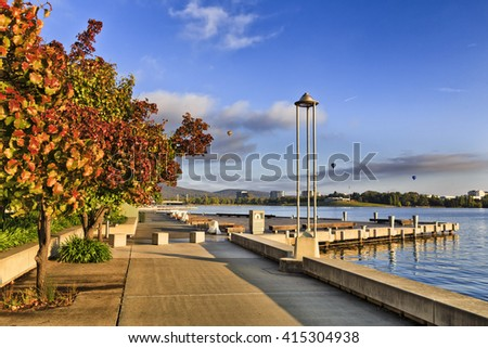 Waterfront boardwalk along autumn foliate trees in red and yellow colours on a warm sunny mornings in Canberra city centre around Burley Griffin lake.