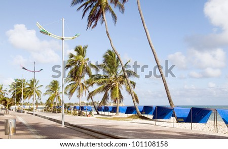 waterfront boardwalk promenade new pedestrian tourist walkway beach palm trees shade huts  San Andres Island Colombia South America - stock photo