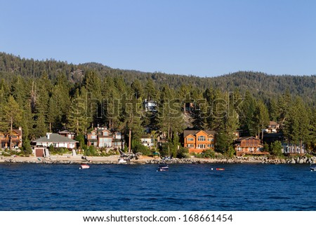 Waterfront homes among the pine trees along the shoreline of Lake Tahoe, Nevada, USA - stock photo