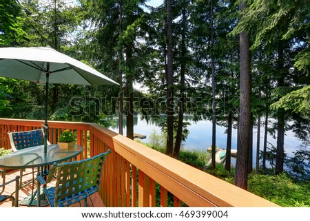 Waterfront lake with small pier. View from balcony with patio area. Northwest, USA