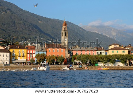 Waterfront of resort-town of Ascona, Ticino, on the shores of  Lake Maggiore featuring the belfry of the Parish Church of Ss. Piedro and Paolo, and the lake facing family-run restaurants. - stock photo