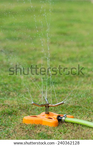 Watering backyard green grass lawn with sprinkler - stock photo