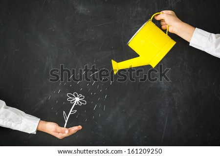Watering can in hand against blackboard - stock photo