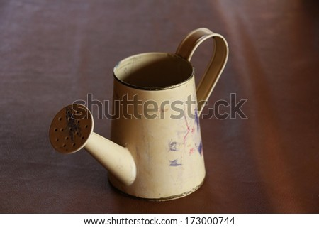 Watering can is placed on the table - stock photo