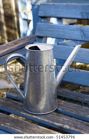 Watering can on bench in the garden
