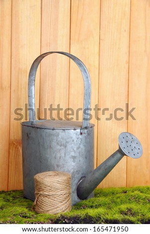 Watering can on grass on wooden background - stock photo