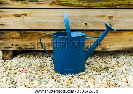 Watering can on stones with wood backdrop in garden