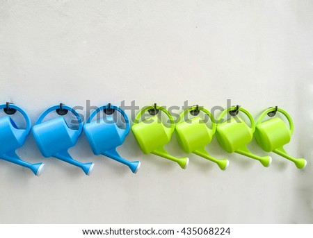 Watering can on white wall - stock photo