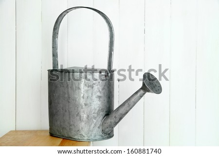 Watering can on wooden background - stock photo