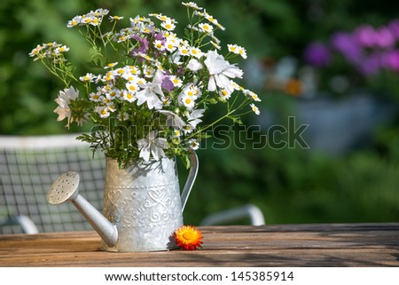 Watering can with garden flowers