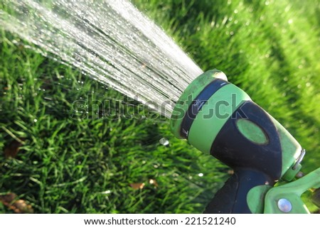 Watering fresh green lawn grass with an adjustable shower (spray) in the summer garden - stock photo