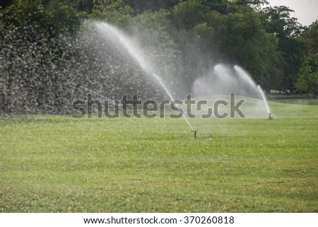 watering in green grass field