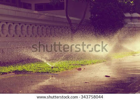 Watering sprinkler on grass field with sunlight at the park , process in vintage style - stock photo
